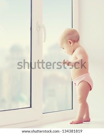 A baby girl looking out the window longing, sadness, and waiting - stock photo