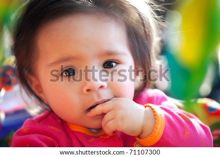 A baby girl looks at the camera with curiosity - stock photo