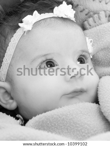 A baby girl looks up at her mother - stock photo