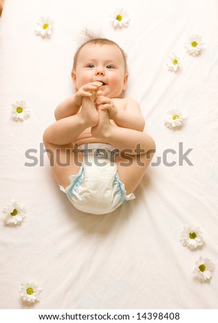 A baby girl lying on a white blanket with white daisies around her. - stock photo
