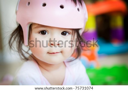 A baby girl with an orthopedic helmet smiles for the camera - stock photo