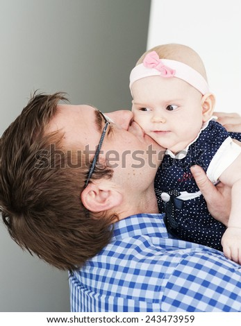 A baby girl with her father - stock photo