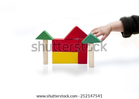 A baby hand is playing toy blocks / construction cubes, isolated on white background - stock photo