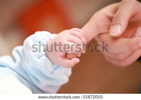 a baby holding his mother's big finger - stock photo