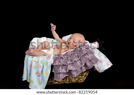 A baby in a laundry basket with her clothes hanging off the sides.