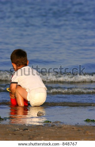 A baby in a nappy on the sea  shore with a red bucket.