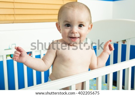 A baby in white crib Nursery interior and bedding for kid - stock photo