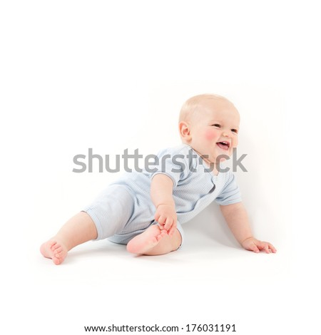 A baby is laughing and playing with his toes.