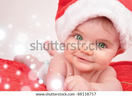 A baby is smiling with a santa hat and sparkles representing christmas magic. Use it for a holiday theme.