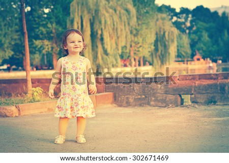 A baby on the background of nature. Child near the lake. Kid walking on the street in the summer. Summer scene with little girl. Summertime, springtime Concept of childhood - stock photo