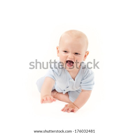 A baby on the floor reaching with one hand. - stock photo