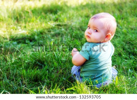 A baby or toddler boy outside in the grass looking back over his shoulder at the camera