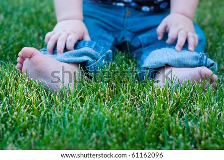 A baby's feet, jeans, and hands sitting in grass.