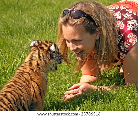 A baby tiger and a smiling pretty woman communicate nose-to-nose - stock photo