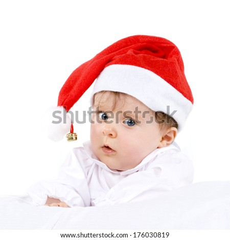 A baby wearing a red Santa hat with a bell on the tassel.