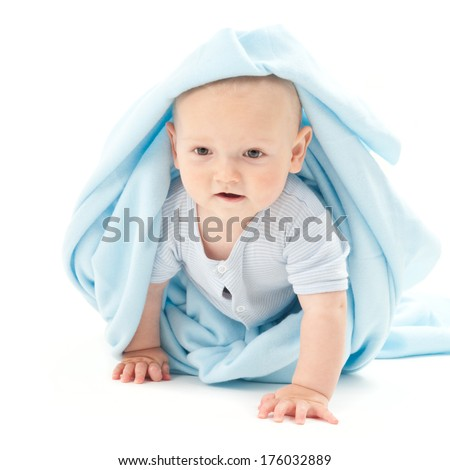 A baby with a blue blanket wrapped around and over the head. - stock photo