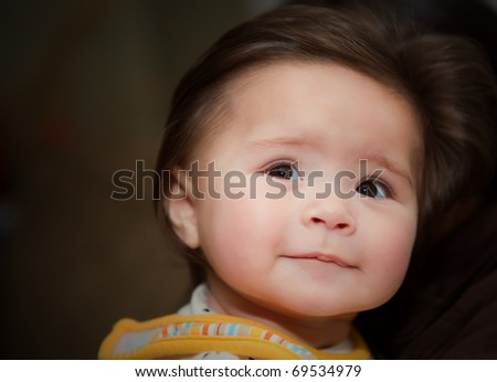 A baby with a hopeful face looking into the future - stock photo