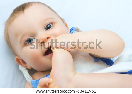 A baby with both hand a feet in mouth