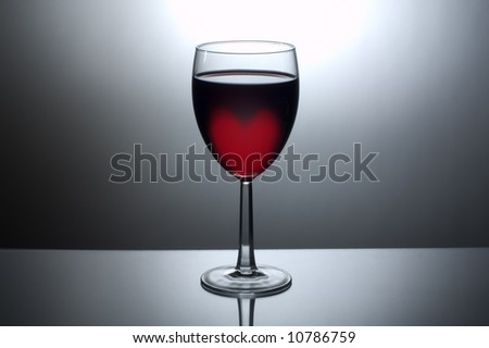A back-lit glass of dark wine with a heart shaped glow in the wine