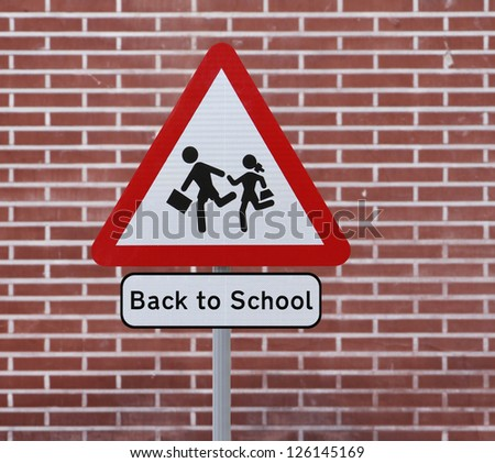 A Back To School road sign with a brick wall background - stock photo
