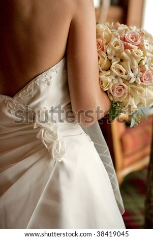 A back view of a bride with her bouquet - stock photo