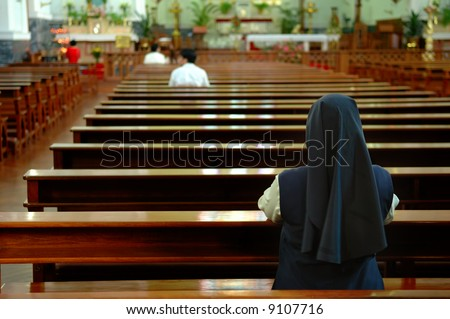 A back view of praying sister inside church - stock photo