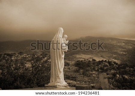 A back view of Virgin Mary holding Baby Jesus in sepia.  - stock photo