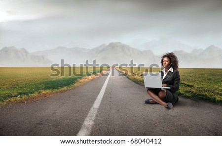 A back woman is working at her laptop on the road - stock photo