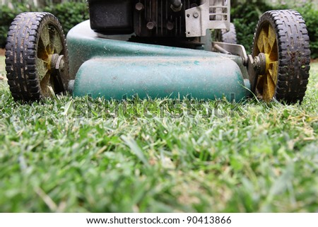 A back yard lawn mower cutting the grass. - stock photo