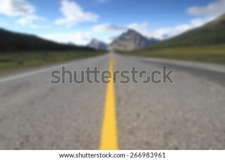A background blur of an empty road leading off into the mountains - stock photo