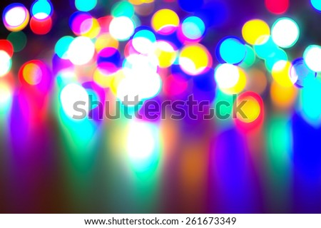 A background composed of colorful blurred light spots on a reflecting ground - stock photo