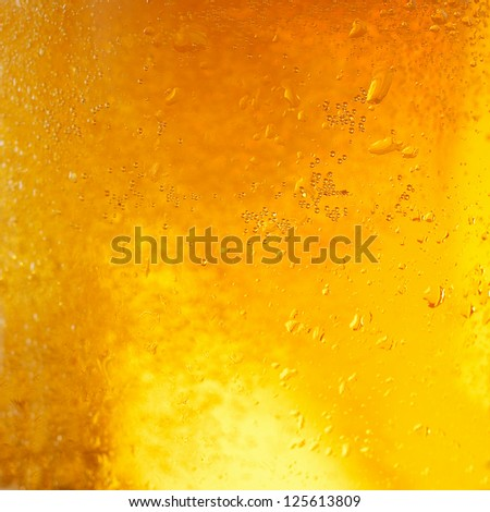 A background created from a closeup of cold light beer in a glass, with condensation droplets on the outside of the glass - stock photo
