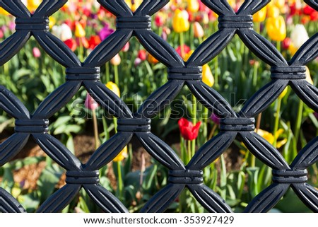 A background of a black metal pattern with soft blurred flowers behind. - stock photo