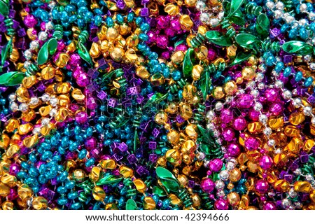 A background of colorful mardi gras beads including gold, blue, green, pink and purple