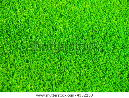 A background of green artificial grass. Shallow DOF.