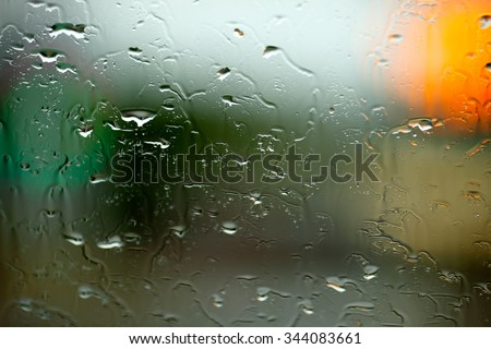 A background of lights blurred by a rain drenched glass window.