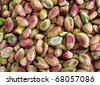 A background of unsalted green pistachio nuts. - stock
