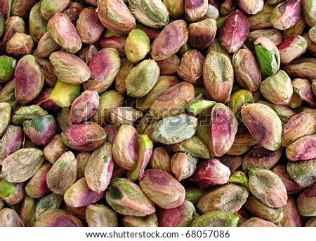 A background of unsalted green pistachio nuts.