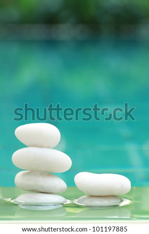 a background stacks of white stones reflected in a pool - stock photo