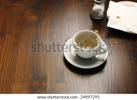 A background with a view of an empty coffee cup on a wooden table. - stock photo