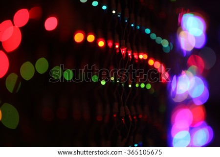 A background with a view of colorful wire mesh, on the backdrop of blur colorful lights during a festival.