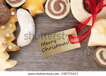 a background with christmas cookies and a golden label with merry christmas written on it