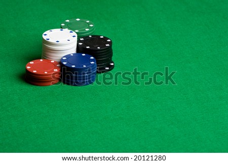A background with poker chips and green felt - stock photo