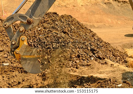 A backhoe and crew dig a utility trench for gas and other electrical utilities at a new commercial construction development - stock photo