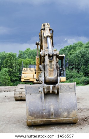 A Backhoe parked at the construction scene - storm brewing - cloudy dramatic sky. - stock photo