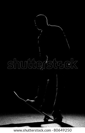 A backlit skateboarder guy posing under dramatic rim lighting with his skateboard flipped up in the front. - stock photo