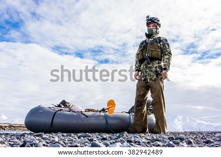 A backpack hunter covered in gear prepares to float in a packraft out of the mountains near the Arctic National Wildlife Refuge in Alaska - stock photo