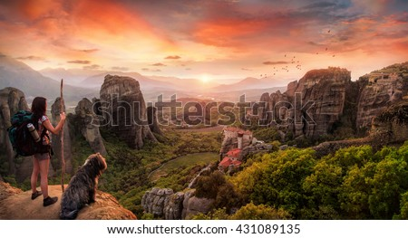 A backpacker and a dog in a breathtaking landscape - stock photo