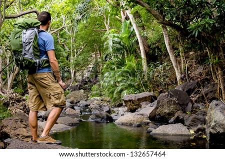 A backpacker in jungle next to river in Hawaii.