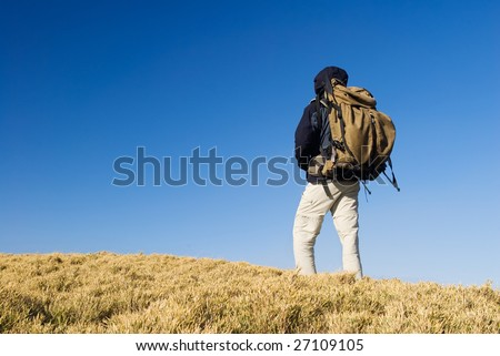 A backpacker walk on a yellow grassland in mountain. - stock photo